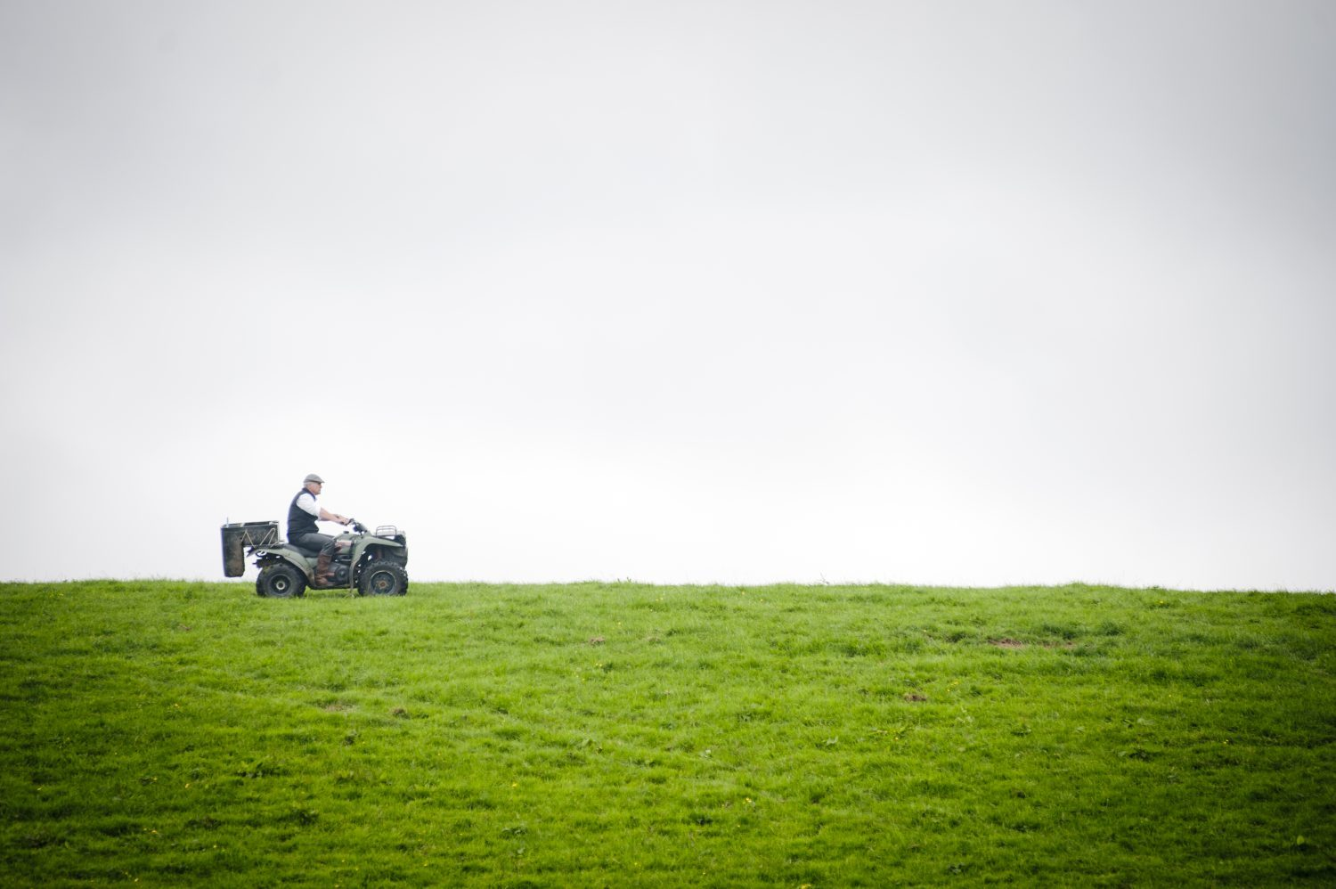 dairy farmer inspecting his grass fields on a quad bike.